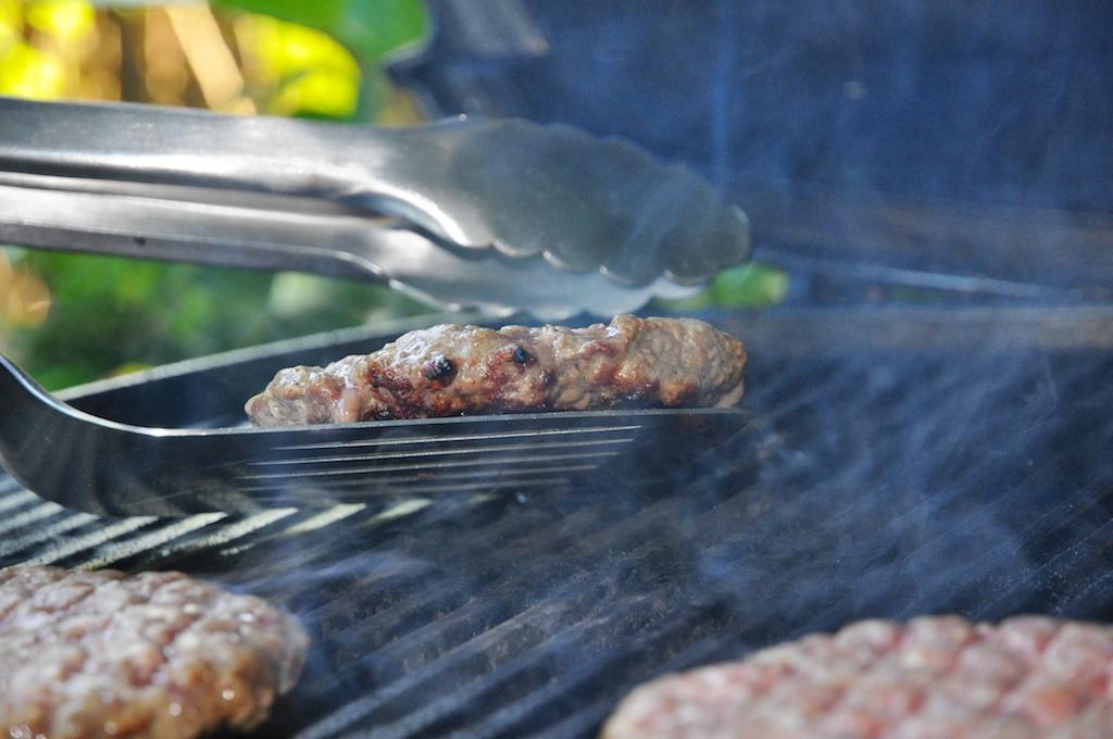 Hamburger auf dem Grill wenden